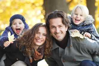 Portrait of a happy family in autumn park with maple leaves