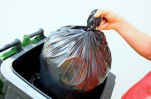 jeter son sac poubelle noir dans un container
